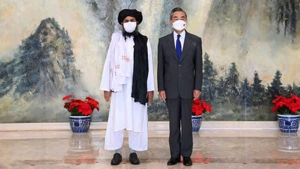 Taliban co-founder Mullah Abdul Ghani Baradar, left, and Chinese Foreign Minister Wang Yi pose for a photo during their meeting in Tianjin, China.